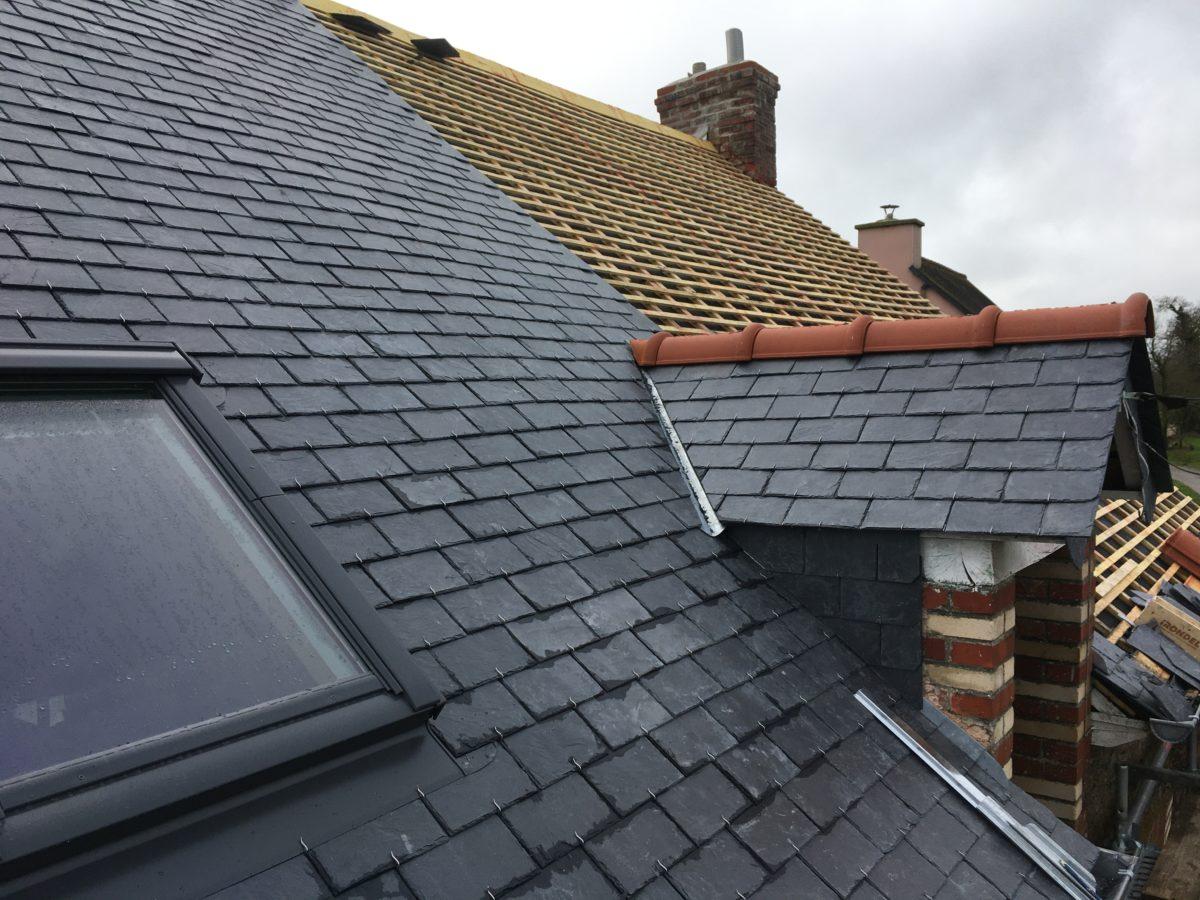 Une toiture en rénovation moitié couverte neuve et moitié litonnée avec lucarne couverte