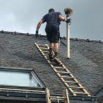 pendant un ramonage par le haut couvreur sur le toit